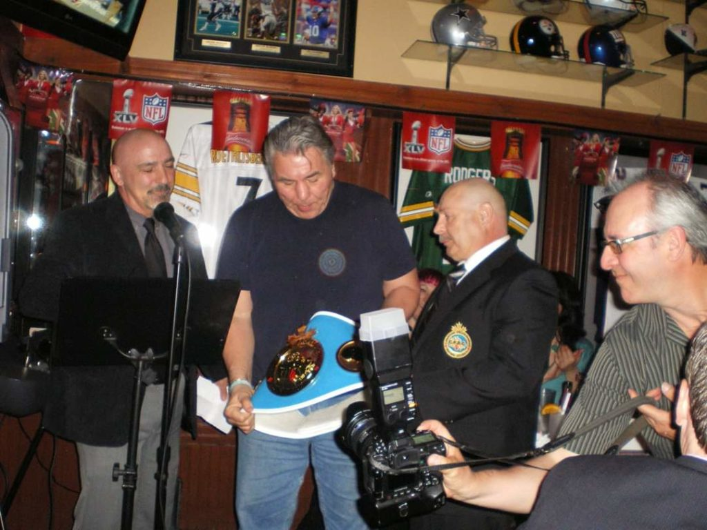 "Mr. Donnie Collette pictured with Georges Doiron presenting Mr. George Chuvalo with a Lifetime Championship Belt at the"" Dining with George Chuvalo"" event held at the Dieppe Sports Rock"" on May 27, 2011."